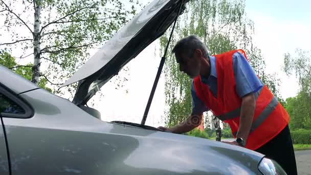 Senior man wears warning vest and controls engine of the car - trees in the background