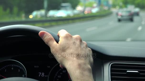 Senior man drives a car - closeup of hand on the steering wheel and road with cars in the background
