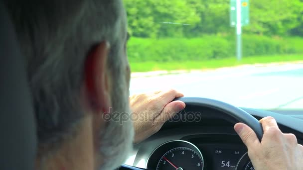 Senior man drives a car - closeup of hands on the steering wheel and speedometer - shot over shoulder