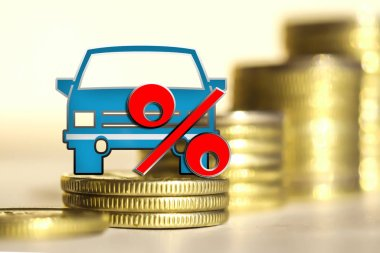 Passenger car and red percent sign on a background of money .