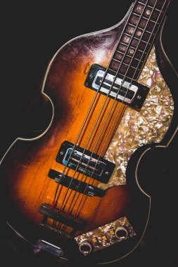 A beautiful brown guitar with a black background.