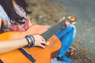 Playing the guitar, hand in bracelets and rings