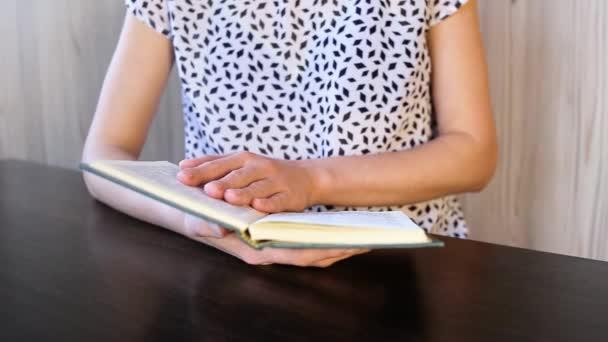 Das Mädchen am Tisch liest die Bibel.