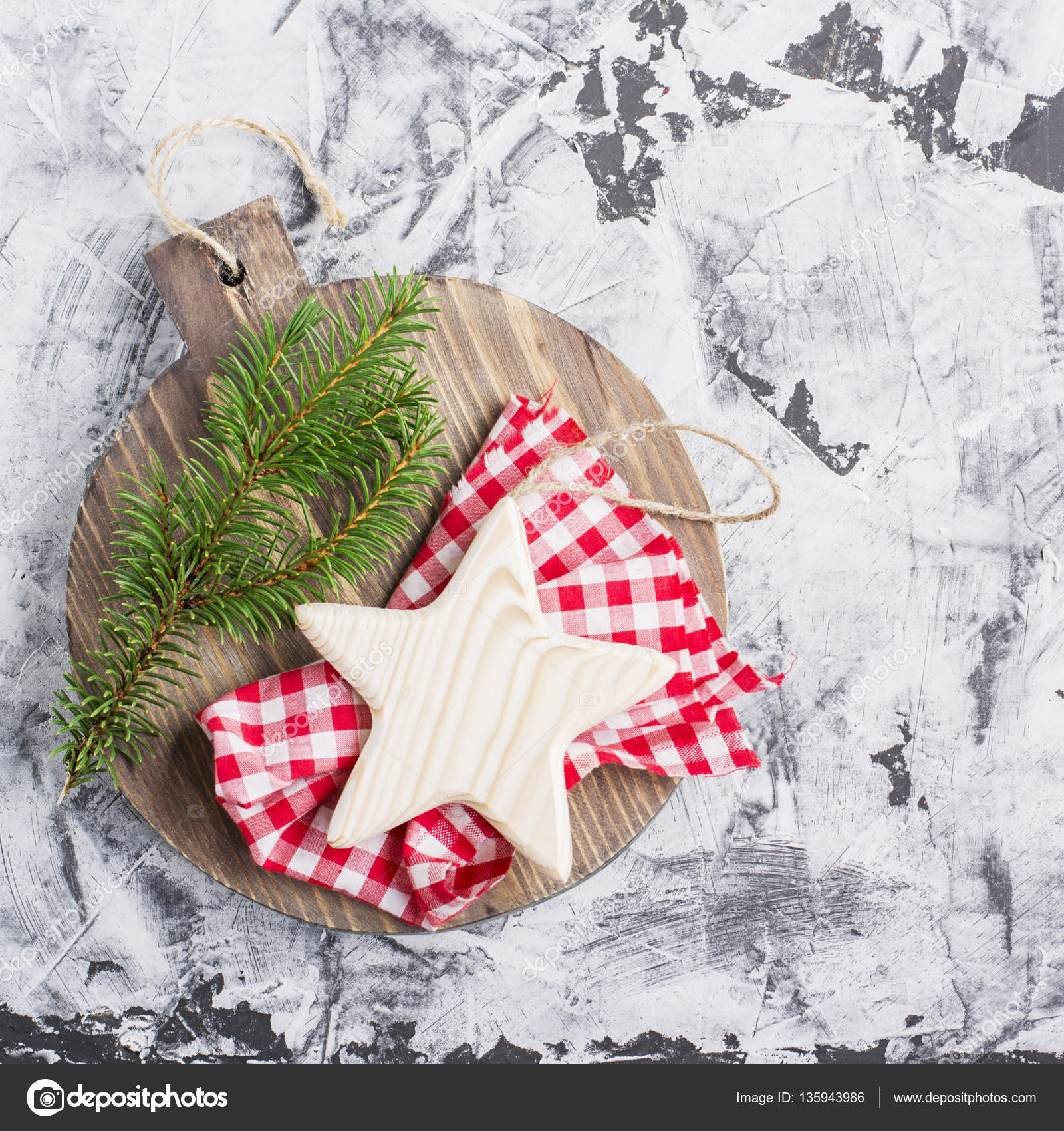 simple christmas background with a wooden board star and fir branch on light gray marble