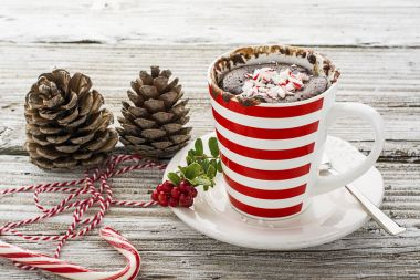 A mug cake for a festive New Year's Eve snack with red white sweets in a striped red white mug on a gray stone background with winter paraphernalia. Selective focus.
