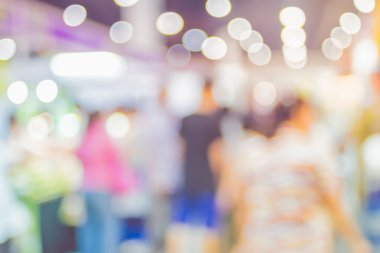 Blurred background: crowd of people in expo fair with bokeh ligh