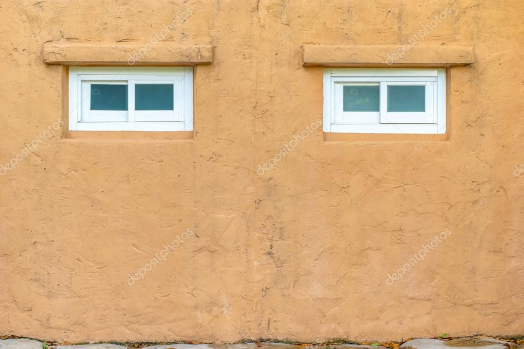 Stucco orange wall with white window texture background