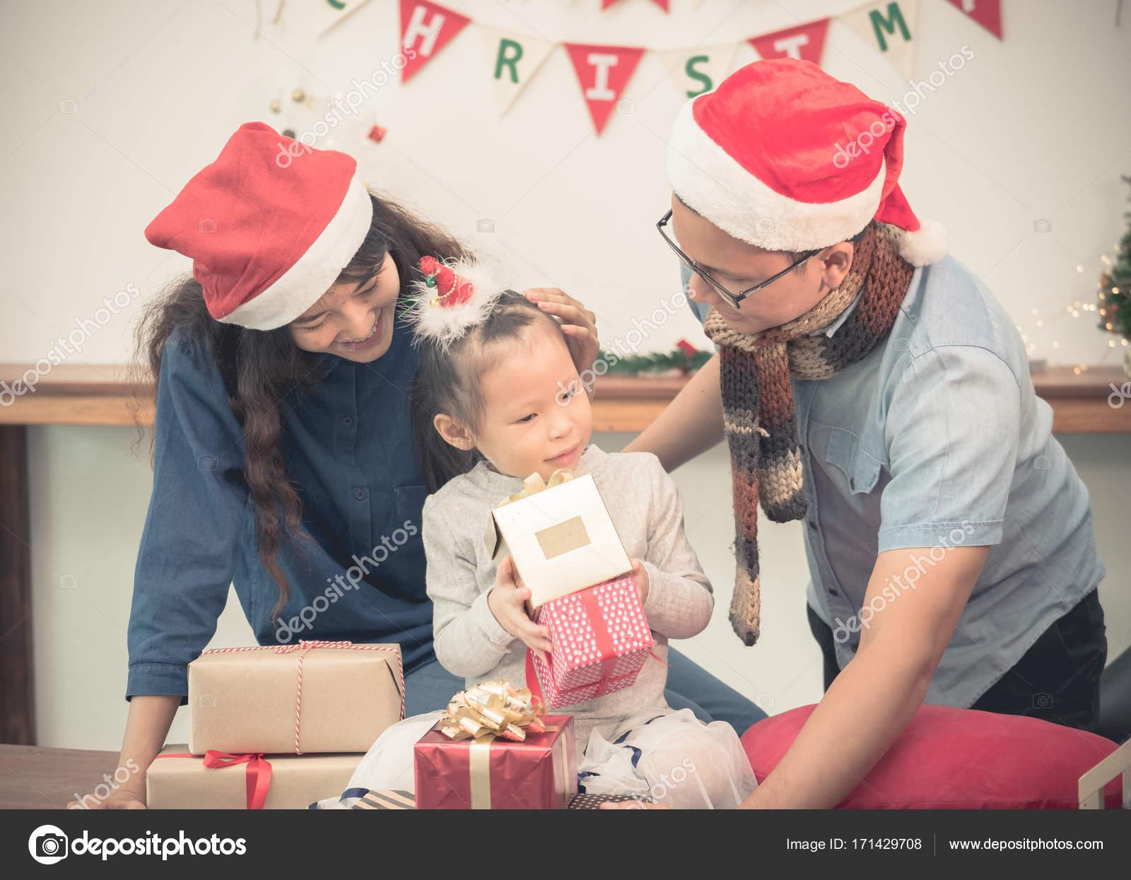 Gelukkige familie asia familie slijtage kerstman hoed uitpakken