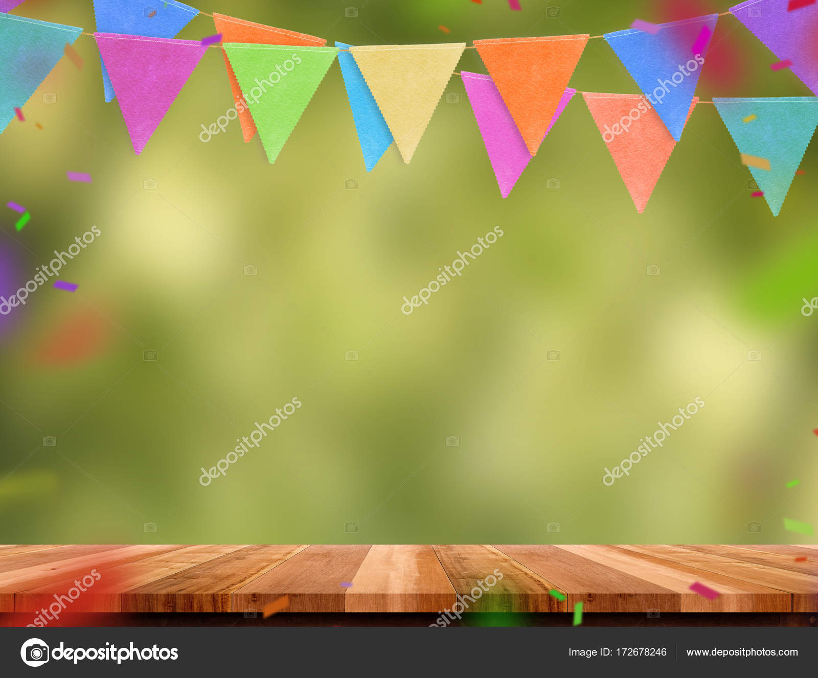 colorful flag banner and confetti on wood table with blur green