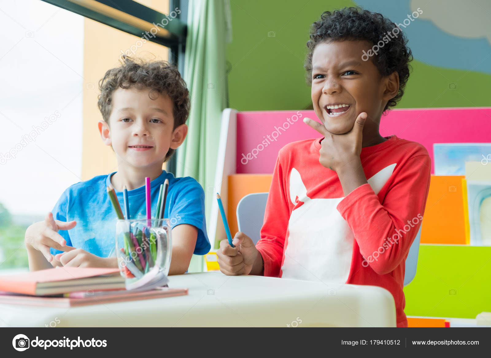 Dos chico kid sit en mesa y el colorante en libro en preescolar libr ...