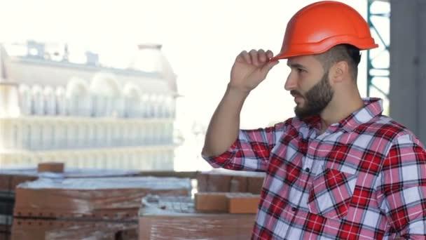 Mužský tvůrce opravuje svůj tvrdý klobouk v budově, ve které se stavebnictví