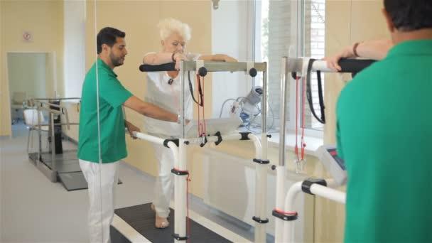 Starší žena jde na běžecký pás rehabilition