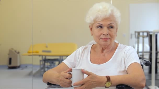 Senior woman keeps cup in her hand