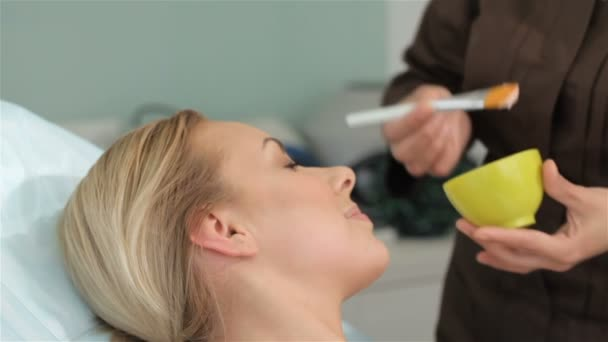 Cosmetologist applies mask on clients face