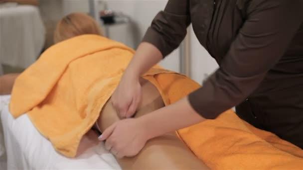 Masíruje klienty stehna uprostřed kosmetologie