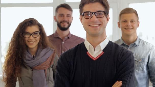Tři muži a jedna žena představují v kanceláři