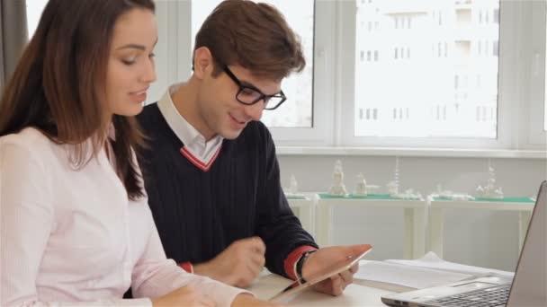 Muž a žena se na mans tabletu v kanceláři
