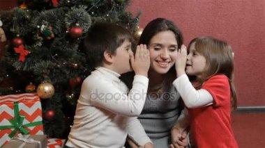 Two kids wisper into womans ears near the christmas tree
