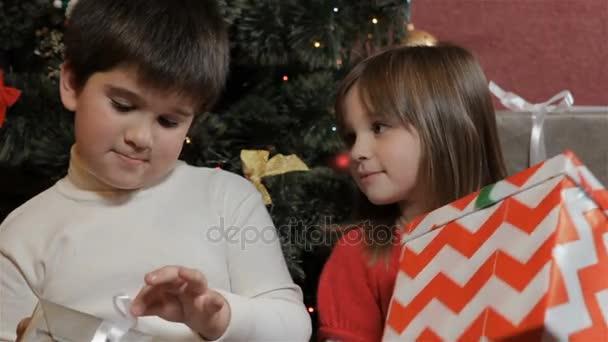 Kinder betrachten ihre Weihnachtsgeschenke