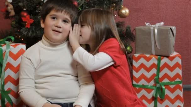 Děti sdílejí tajemství u vánočního stromu