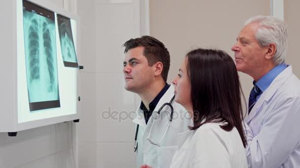 Lékařský tým analizes RTG na rentgenových