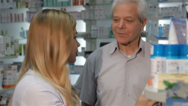 Apothekerin zeigt dem männlichen Kunden Medizin