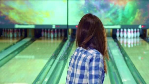 Dívka klepe kolíky na bowling