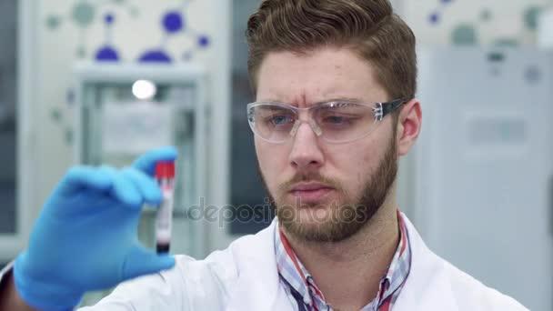 Muž v laboratoři při pohledu na zkumavky
