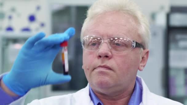 Muž zvedne zkumavky v laboratoři