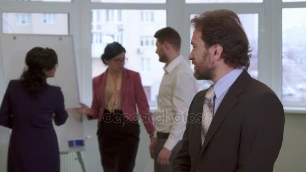Středního věku podnikatel pózy v kanceláři