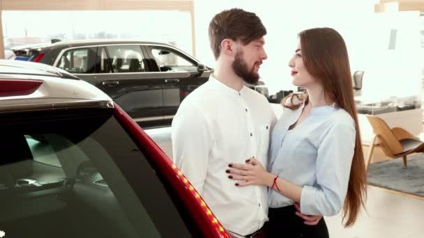 Několik vzájemně obejme poblíž auto u dealera