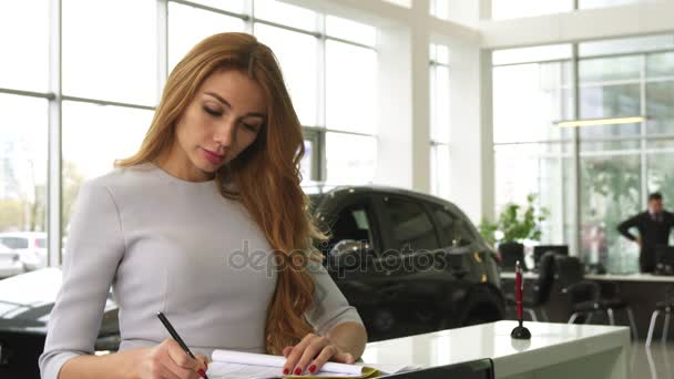 Gorgeous woman buying a new car at the dealership smiling to the camera