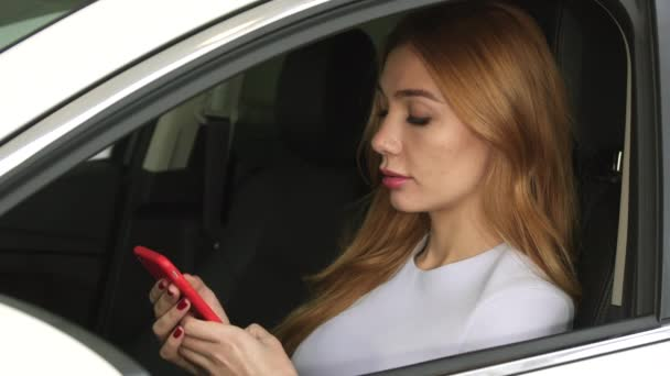 Beautiful young woman using smart phone sitting in her car