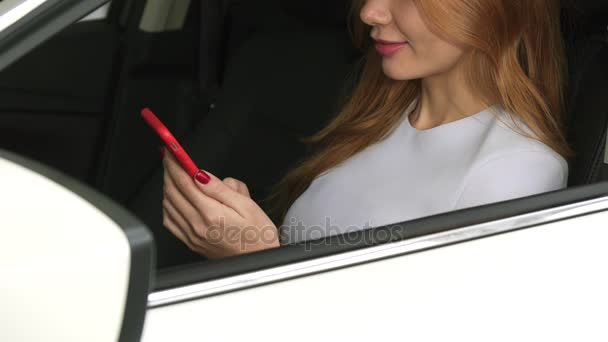 Cropped shot of smiling woman sitting in a car texting on her smart phone