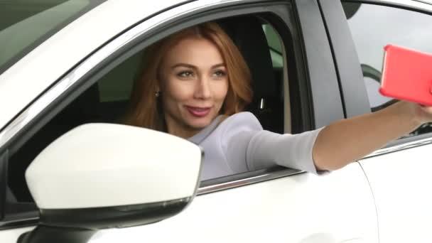Šťastná Mladá krásná žena pořízení selfie sedí v jejím novém autě