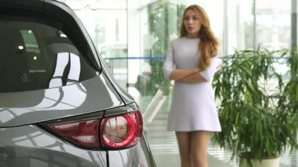 Gyönyörű nő gondolkodás mellett kiválasztás egy új autót a kereskedés