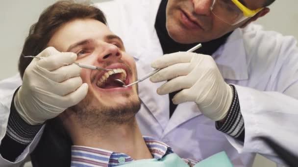 schöner junger Mann lächelt während der Zahnuntersuchung