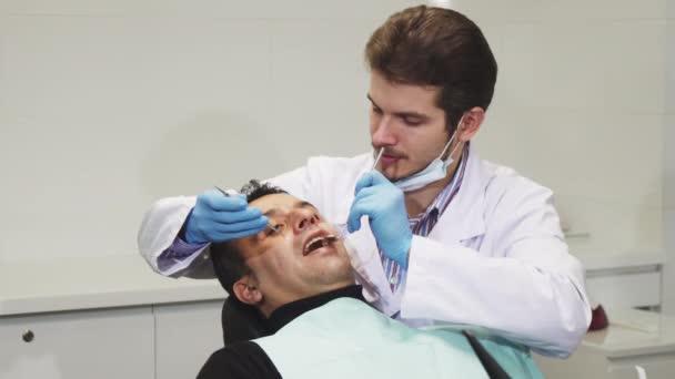 Mladý muž zubař usmívající se během zubní prohlídku svého pacienta