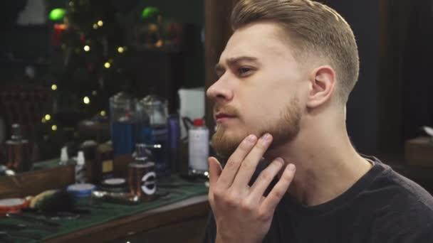 Vousatý muž zkoumá svůj nový účes v holičství