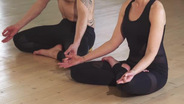 Beautiful couple meditating together doing yoga