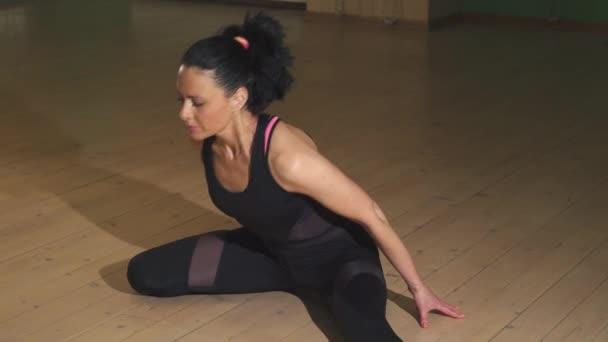 Atraktivní veselá žena táhnoucí se doma dělat jógu
