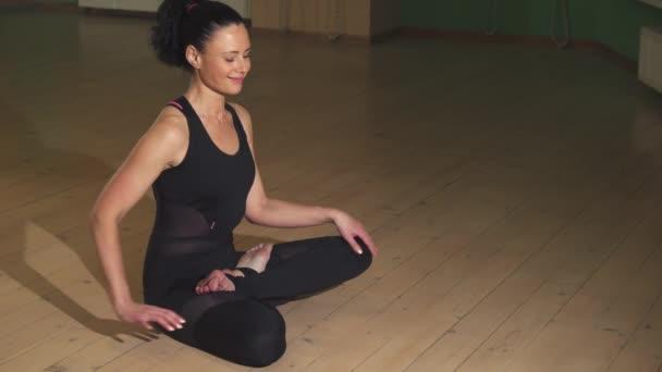 Uvolněná krásná šťastná žena cvičí jógu večer doma