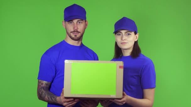 Dva šťastné profesionální pracovníci podal balíček box kamery