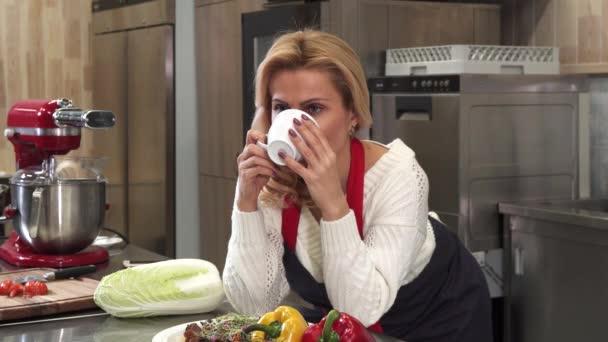 Atraktivní starší žena s kávou v kuchyni doma