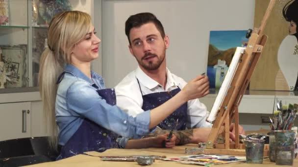 Liebendes junges Paar genießt die gemeinsame Arbeit an einem Gemälde im Kunstatelier