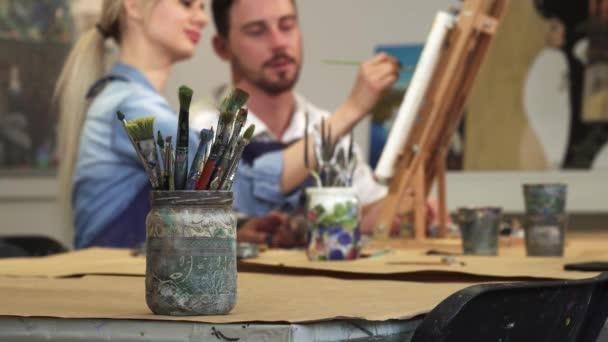junges Paar arbeitet gemeinsam im Kunstatelier an einem Bild