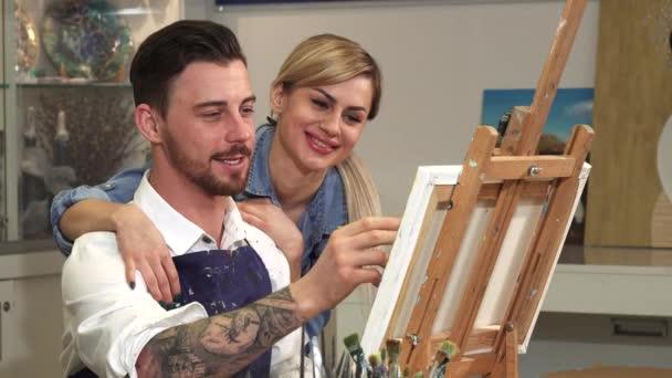 Nahaufnahme eines hübschen Künstlers, der in seinem Atelier zeichnet, während seine Frau ihn umarmt