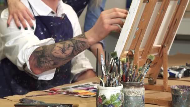 professionelle Künstler Malerei auf Leinwand seine Freundin umarmt ihn