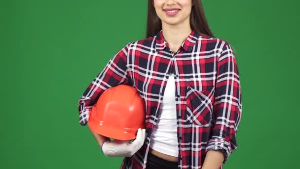 Oříznout záběr usmívající se žena inženýra ukazující thimbs drží bezpečnostní přilba