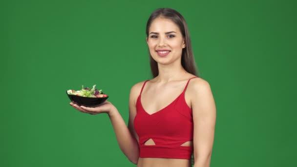 Šťastné mladé fit žena ukazuje ok znamení úsměvu, držící misku čerstvým salátem